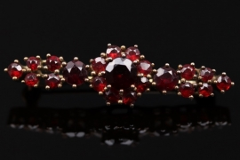 Golden brooch with red garnets