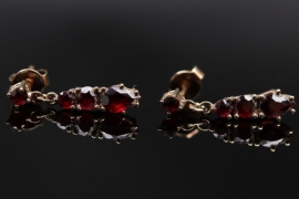 Golden ear studs with red garnets