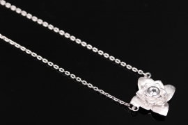 Silver necklace with rose-shaped pendant and white topaz
