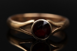 Golden ring with red garnet