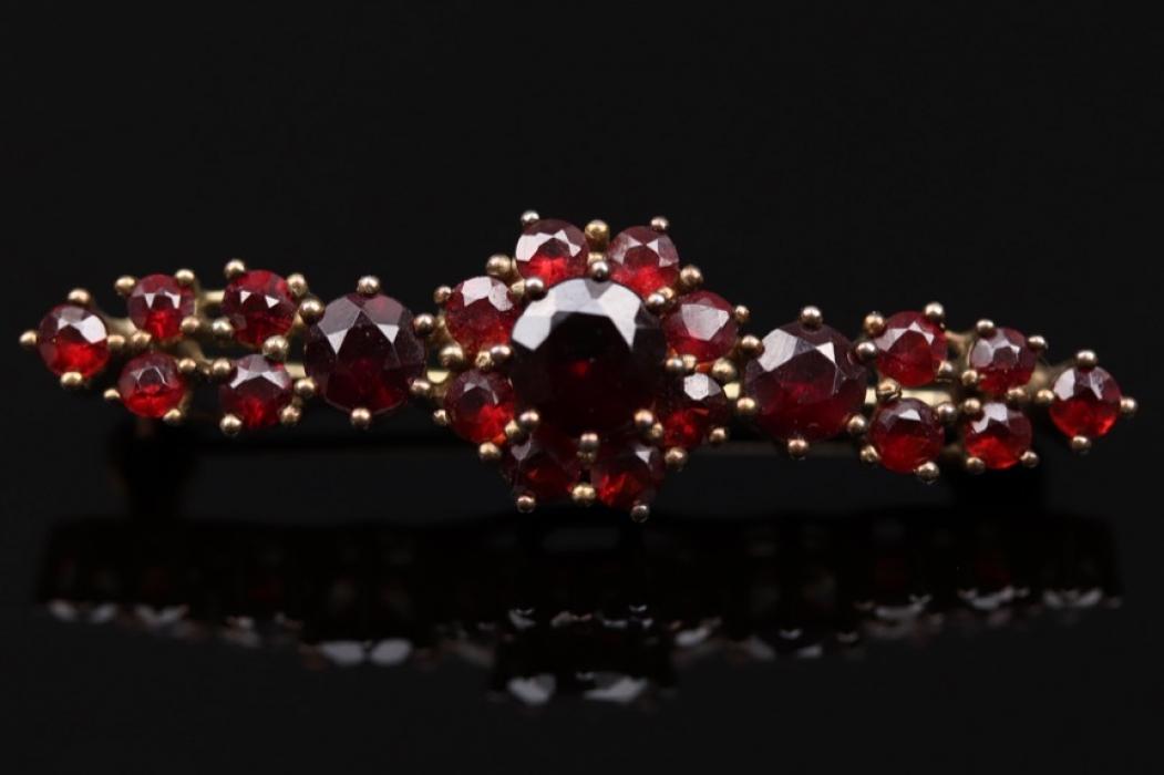Golden brooch with red garnets