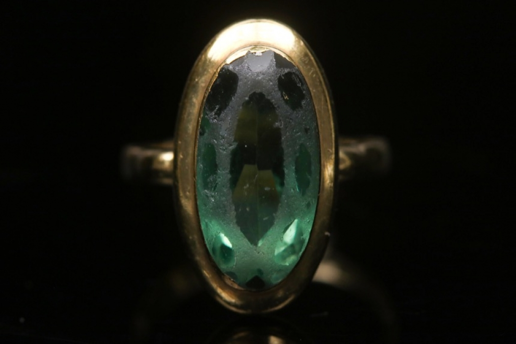 Golden ring with green glass stone